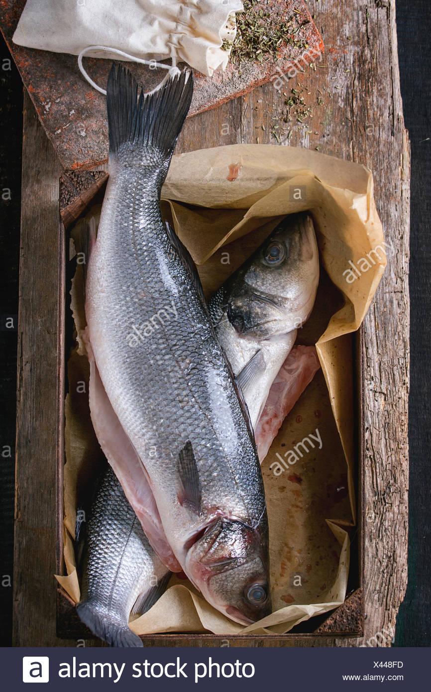 Deux poissons crus crus seebass dans boîte en bois avec des herbes sèches au fond de bois ancien. Vue d'en haut Photo Stock