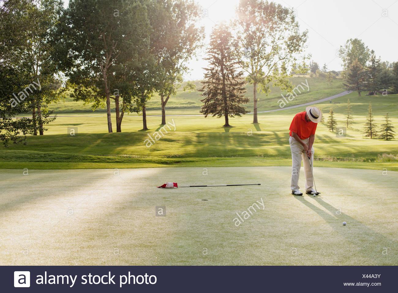Man à propos de putt sur golf green Photo Stock