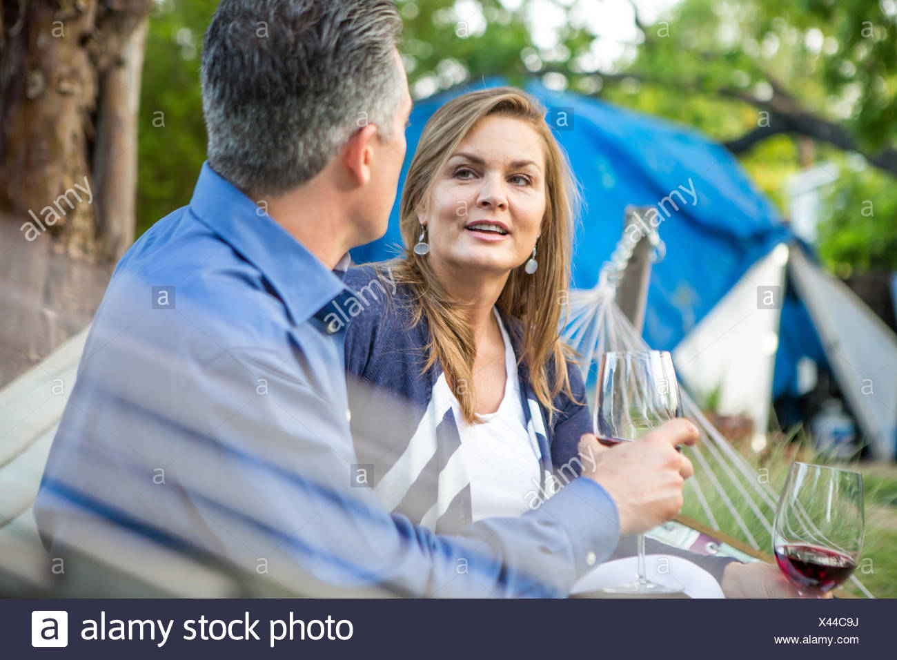 Mature couple chatting on hammock at garden party Photo Stock