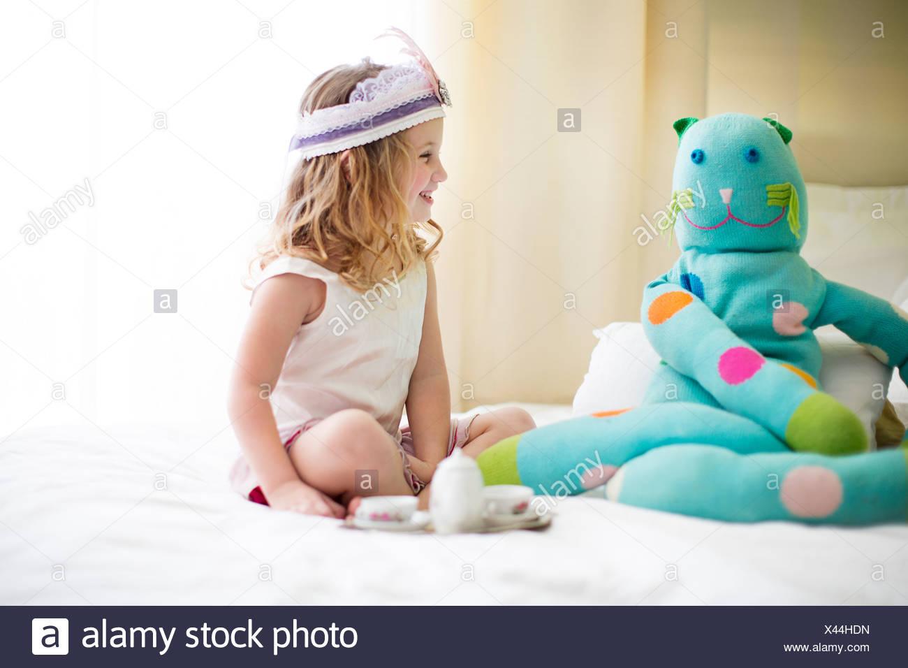 Jeune fille adorable en peluche avec thé partage on bed Photo Stock