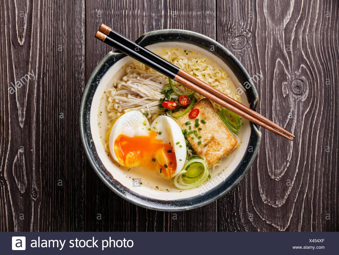Nouilles ramen Miso asiatique avec des œufs, tofu et enokis dans un bol sur fond de bois gris Photo Stock