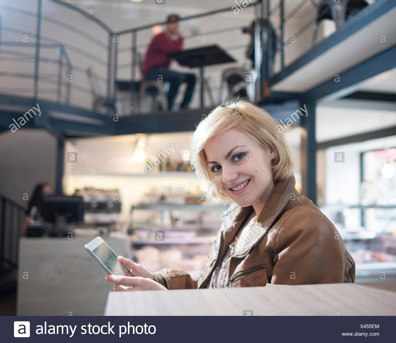 Portrait of smiling young woman using tablet PC in cafe Banque D'Images