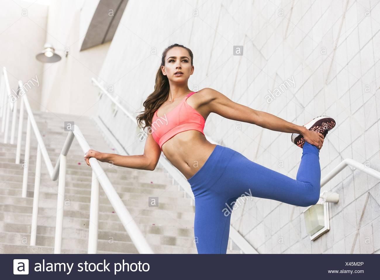 Low angle view of young woman holding qui s'étend de la cheville de la jambe, à l'écart Banque D'Images