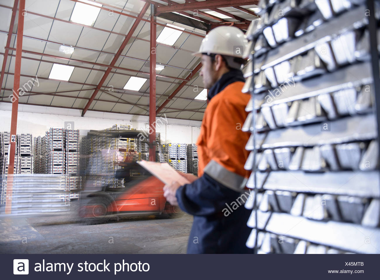 Les employés de l'entrepôt déménagement lingots d'aluminium empilées Photo Stock