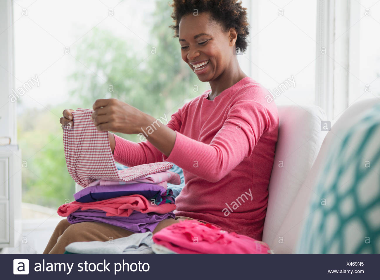 Mid adult woman folding linge propre Photo Stock