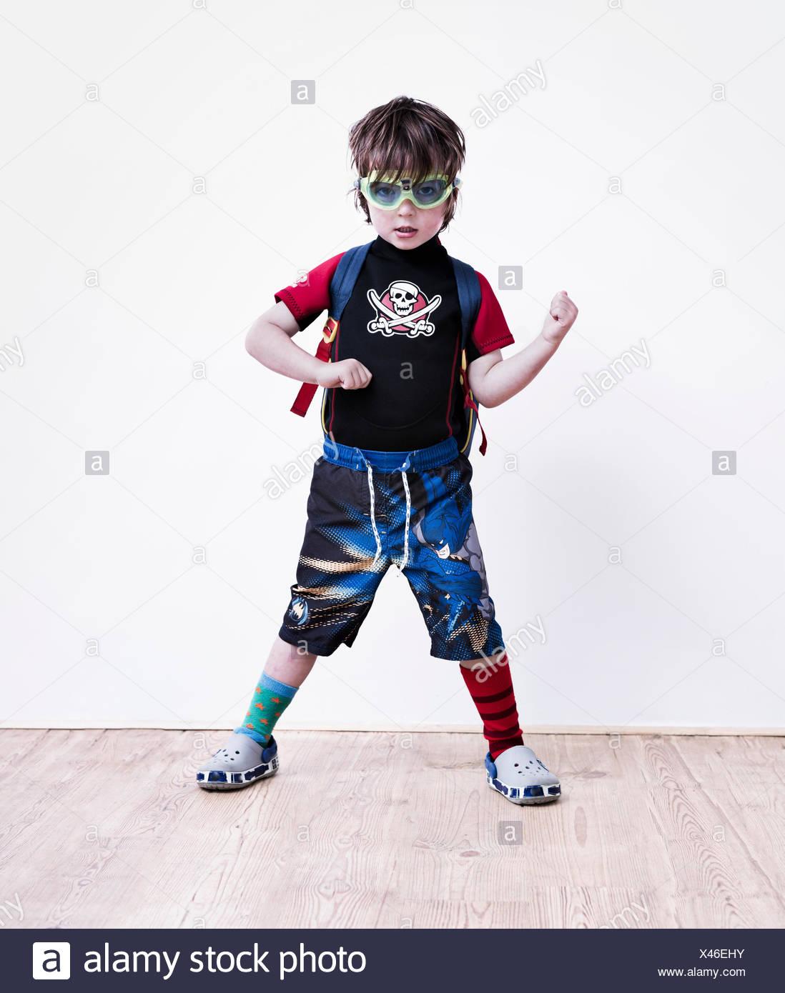 Un garçon debout les jambes écartées posing in fancy dress, vêtu d'un tee-shirt pirate, lunettes et long short. Photo Stock