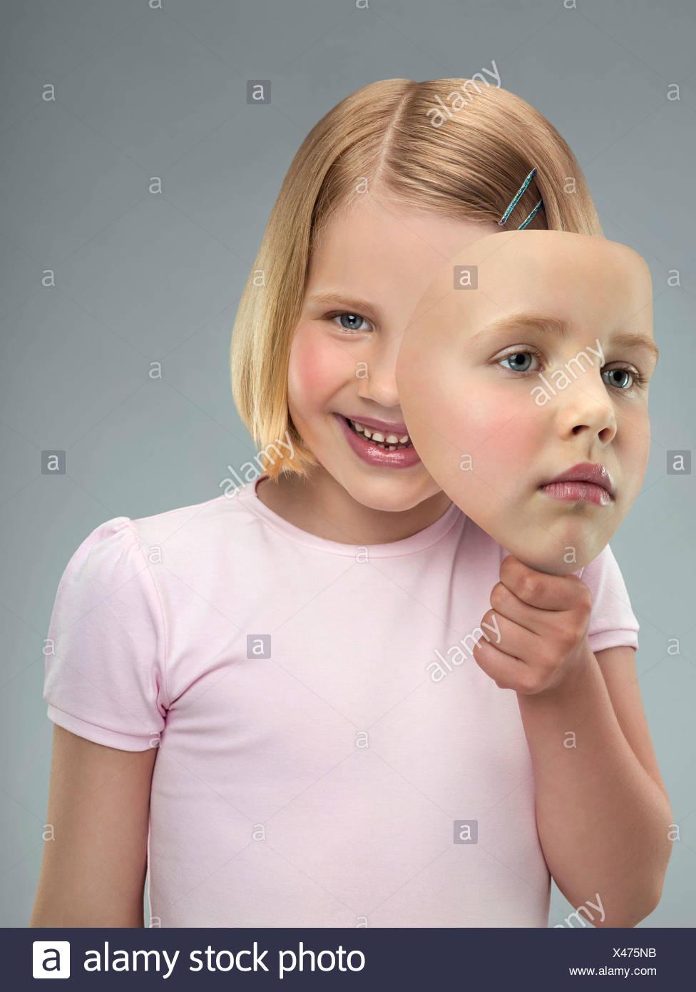 Portrait d'une jeune fille tenant un masque, studio shot Photo Stock