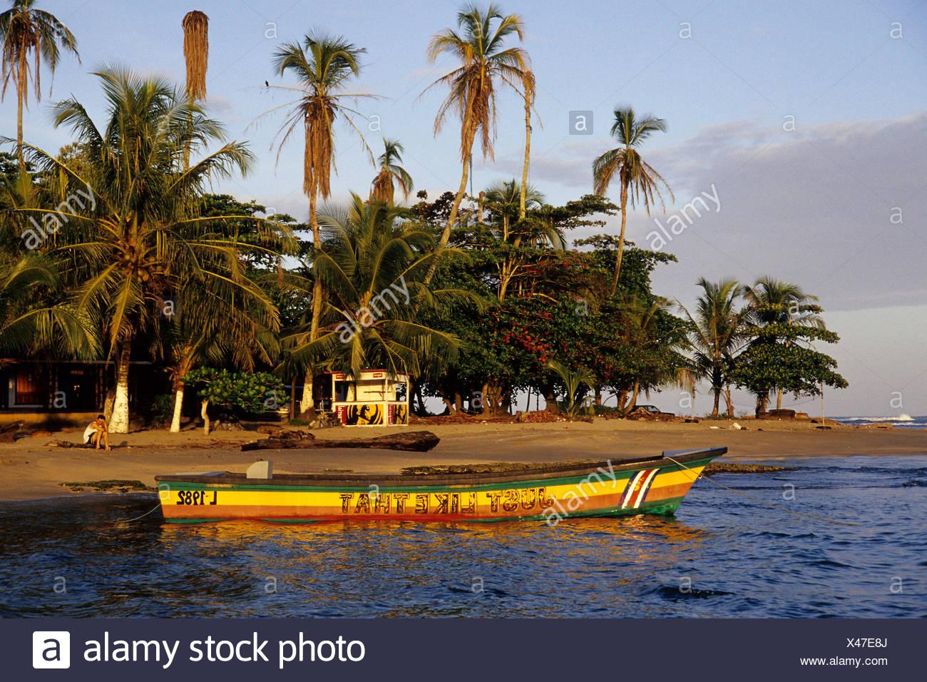 Petit bateau peint en couleurs reggae sur une plage tropicale avec palmiers, Puerto Viejo de Talamanca sur la côte des Caraïbes Photo Stock