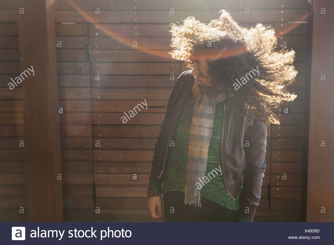 Woman standing outdoors secouant ses cheveux Photo Stock
