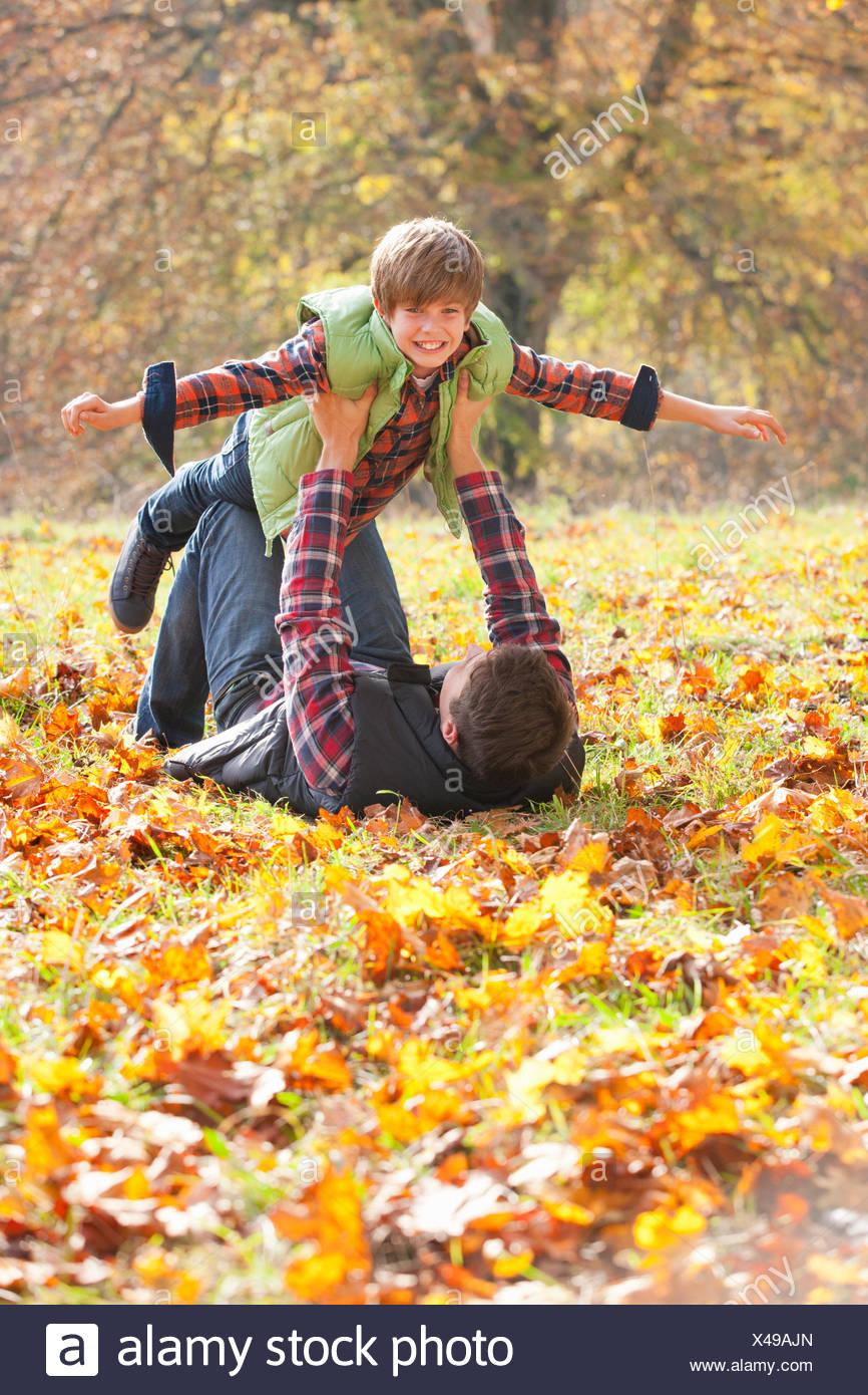 Fils Père tient le haut comme un avion dans le parc en automne Photo Stock