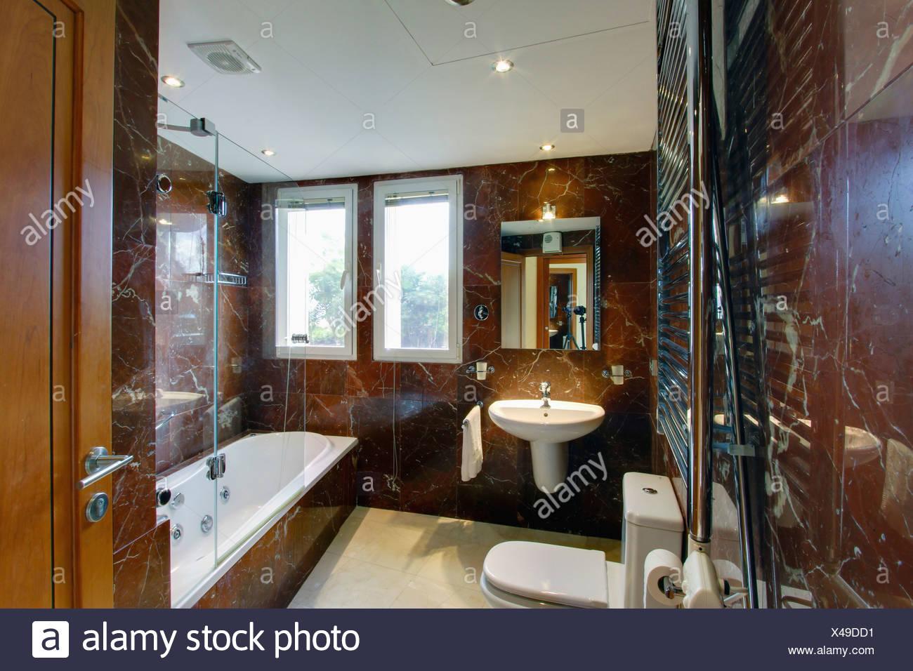 Salle de bains moderne en marbre brun espagnol avec miroir éclairé ...