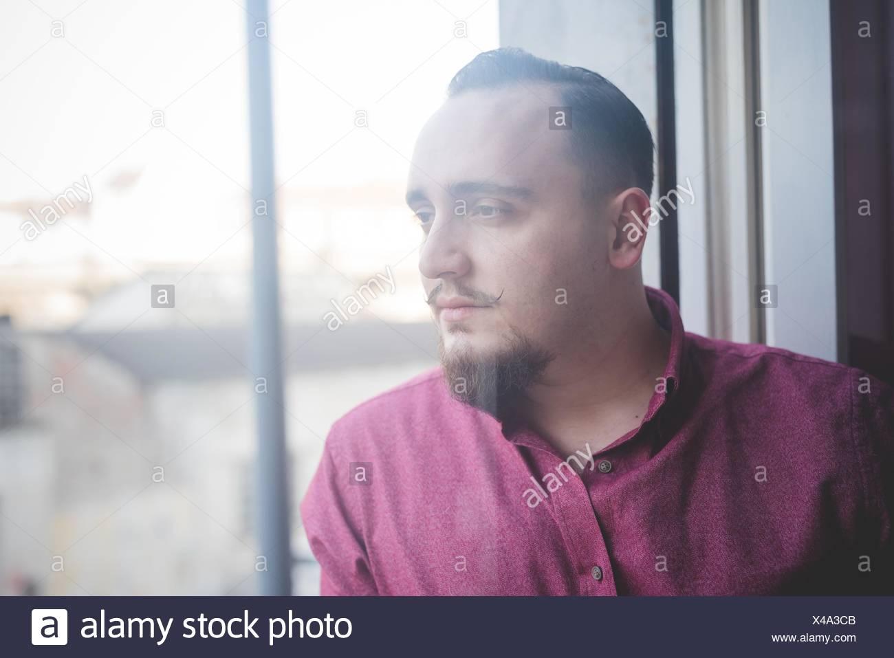 Portrait de jeune homme par fenêtre Photo Stock