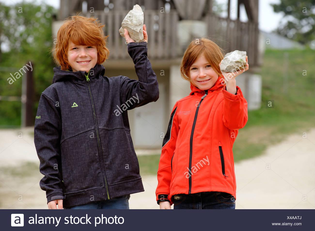 Deux enfants tenant des pierres contenant des fossiles de la rupture des roches en Hohenmirsberger Geozentrum Platte, geo-centre Photo Stock
