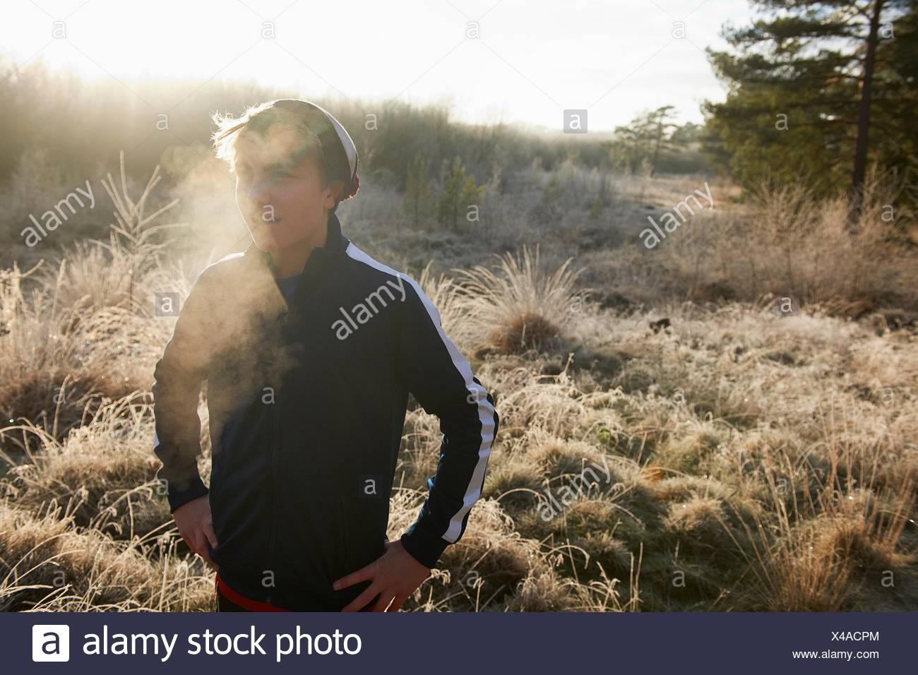 Teenage boy sur prairie givrée visible, souffle, les mains sur les hanches à l'écart Photo Stock