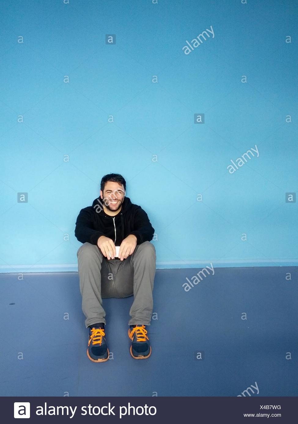 Portrait Of A Smiling Young Man Sitting contre mur bleu Photo Stock