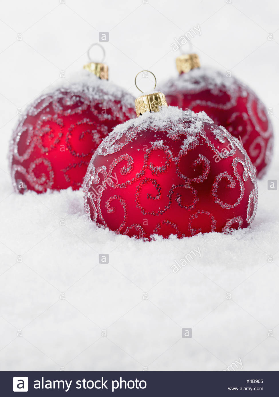Close up of red Christmas Ornaments in snow Photo Stock