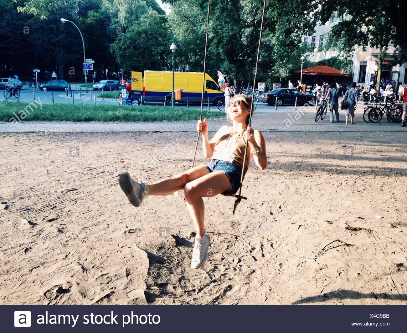 Toute la longueur d'un cute girl Sitting on Swing Photo Stock