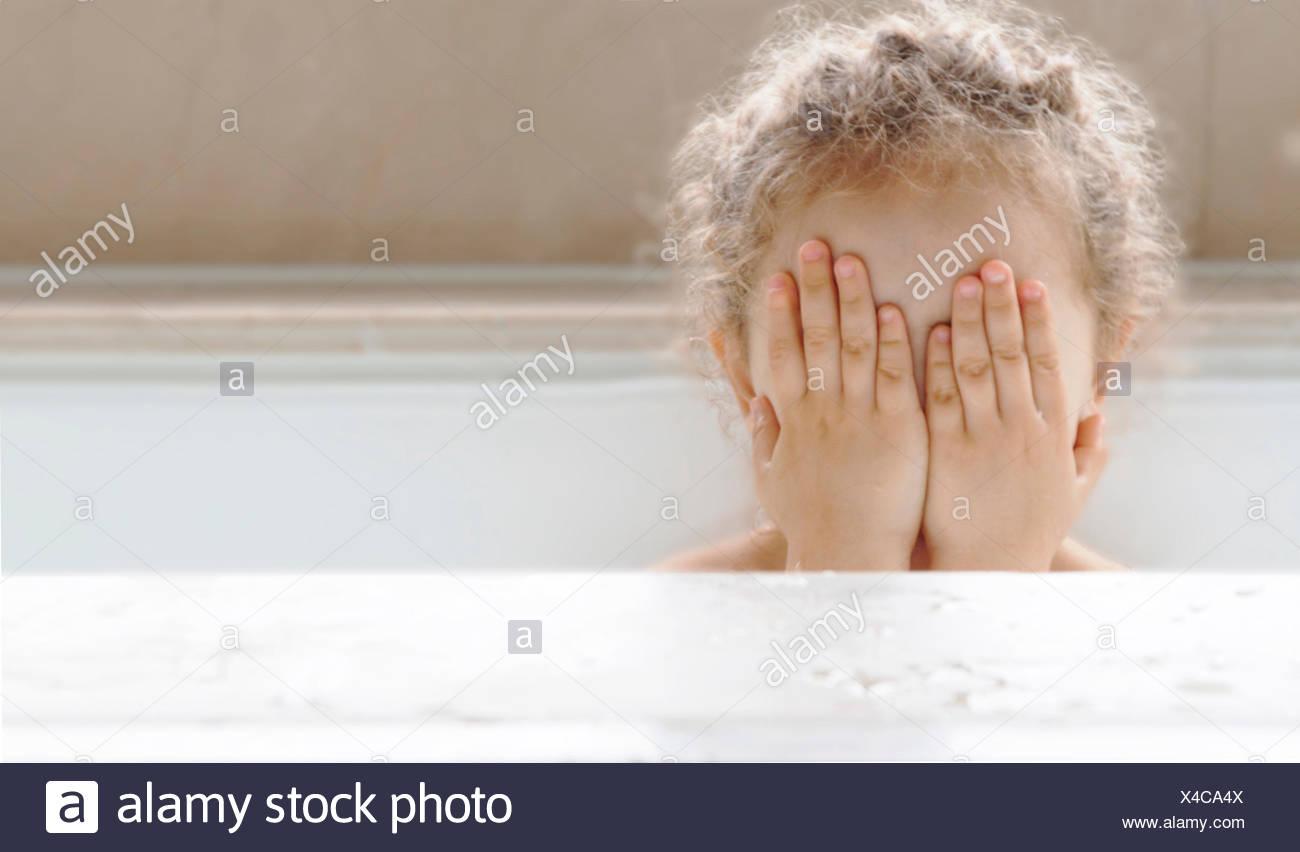Portrait d'une jeune fille assise dans une baignoire couvrant le visage avec ses mains Photo Stock
