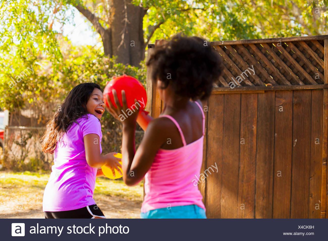 Girl chasing ami ballon avec de l'eau dans le jardin Banque D'Images