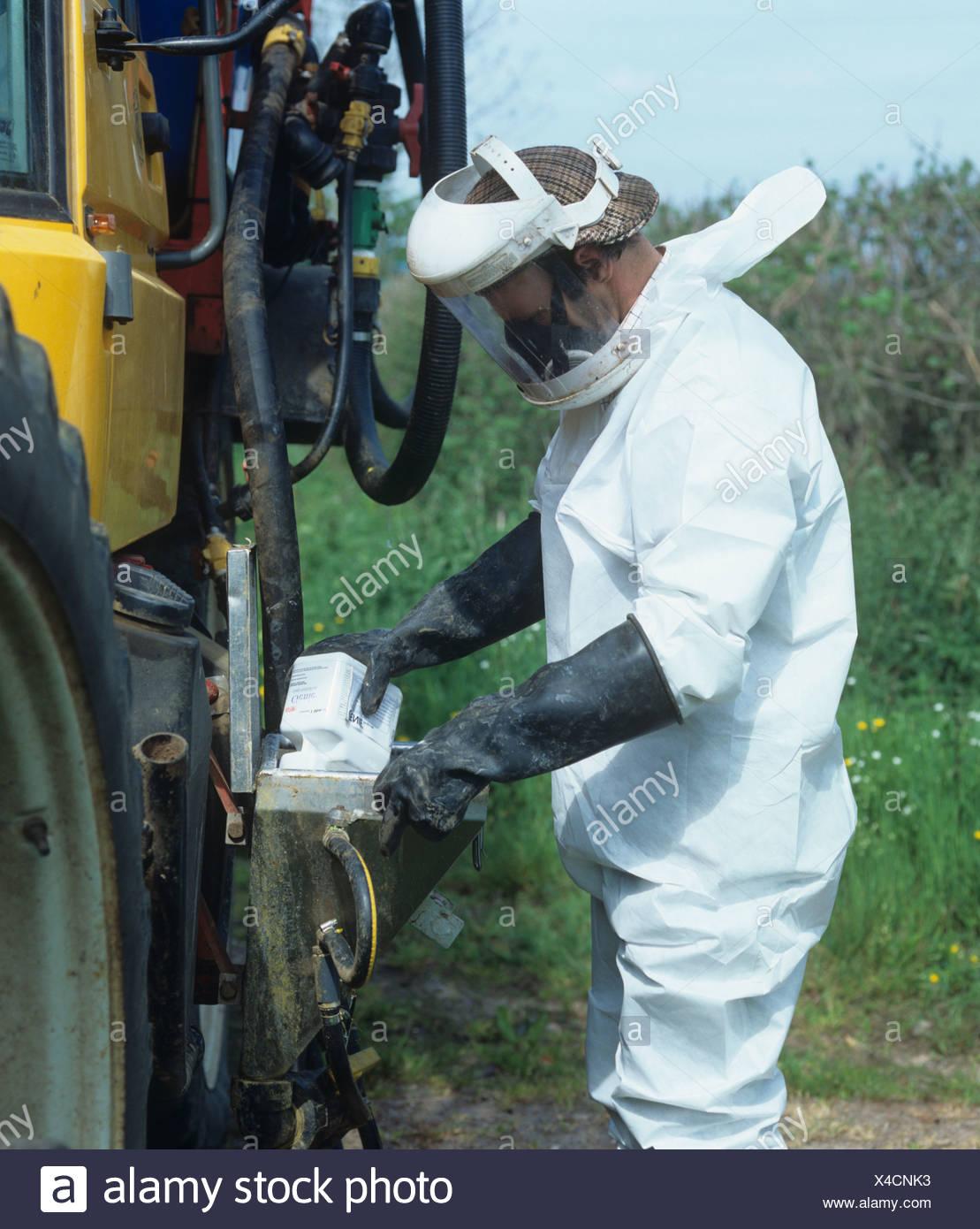 Conducteur de tracteur dans des vêtements de protection complets, l'ajout de produit chimique dans le réservoir d'un pulvérisateur Photo Stock