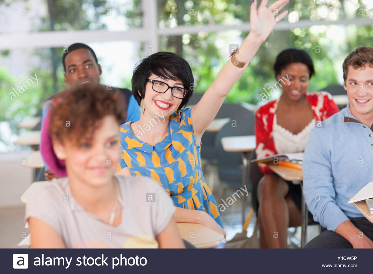Levant la main d'étudiants en classe Photo Stock