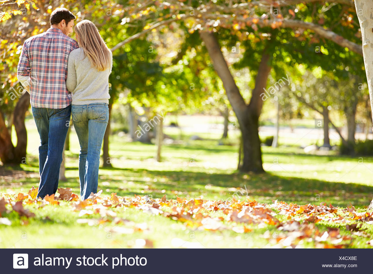 Vue arrière du couple romantique marche à travers bois d'automne Photo Stock