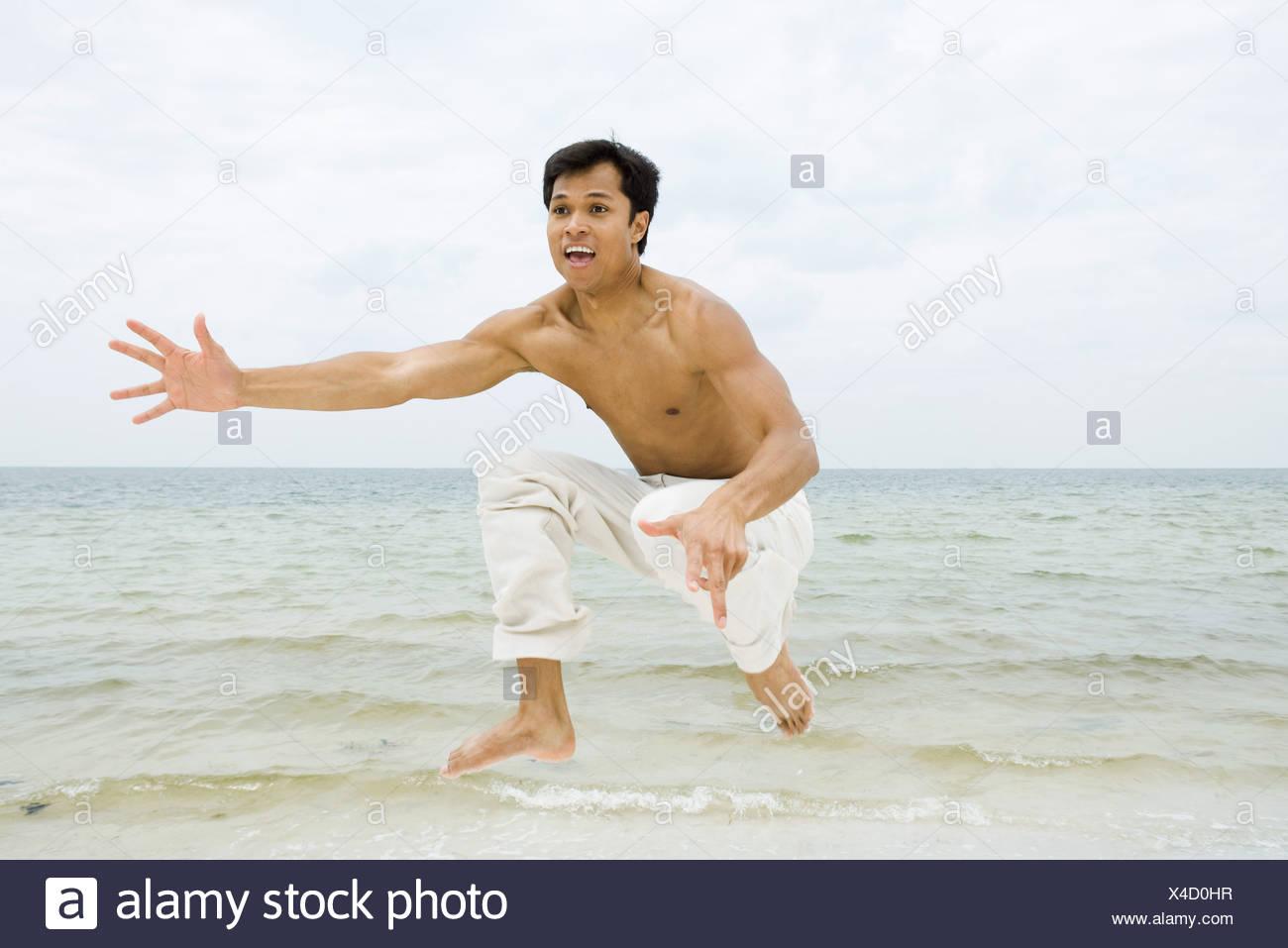 Man dans l'air et de crier, de l'océan en arrière-plan Banque D'Images