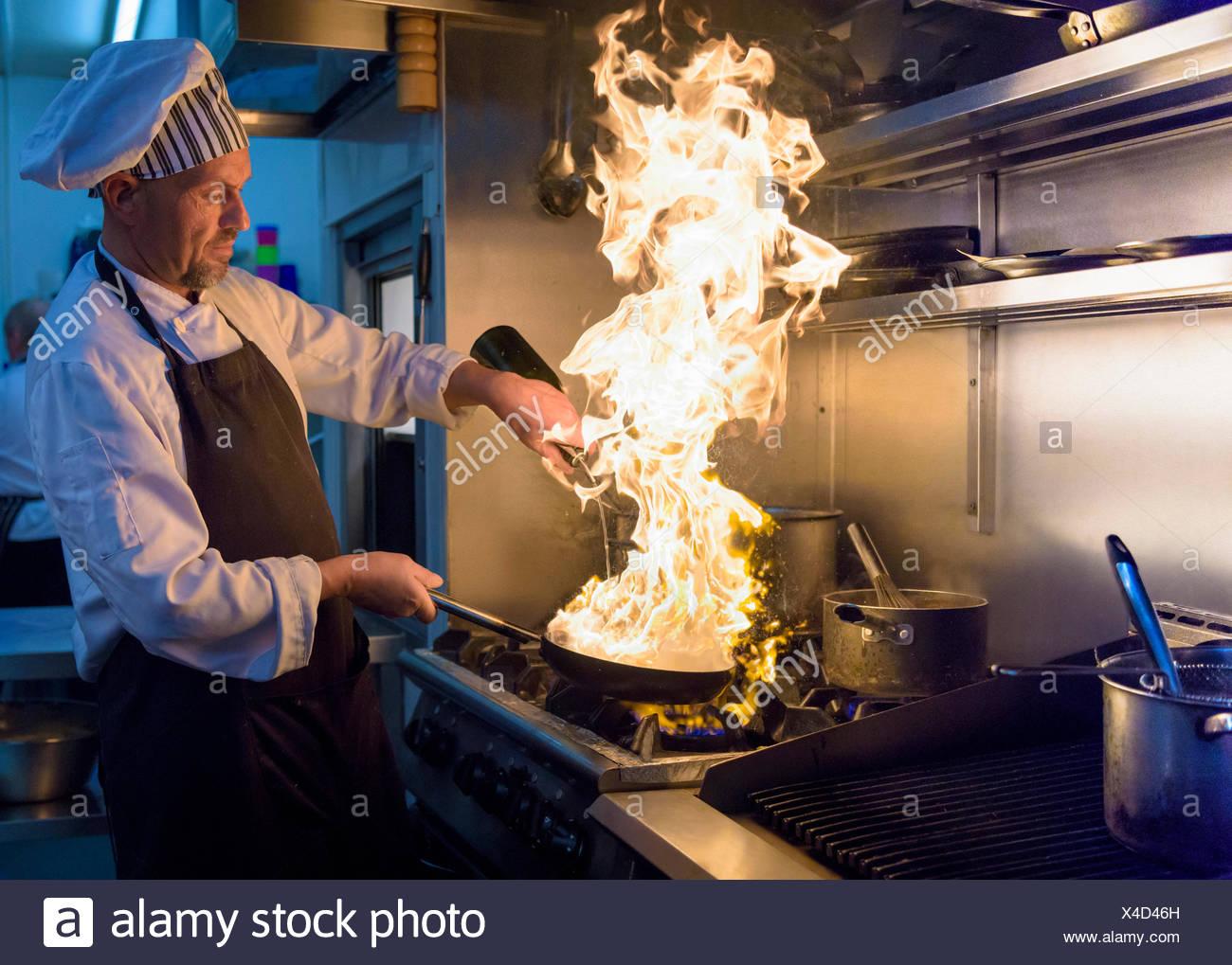 Chef avec pan de flammes dans la cuisine restaurant traditionnel italien Photo Stock