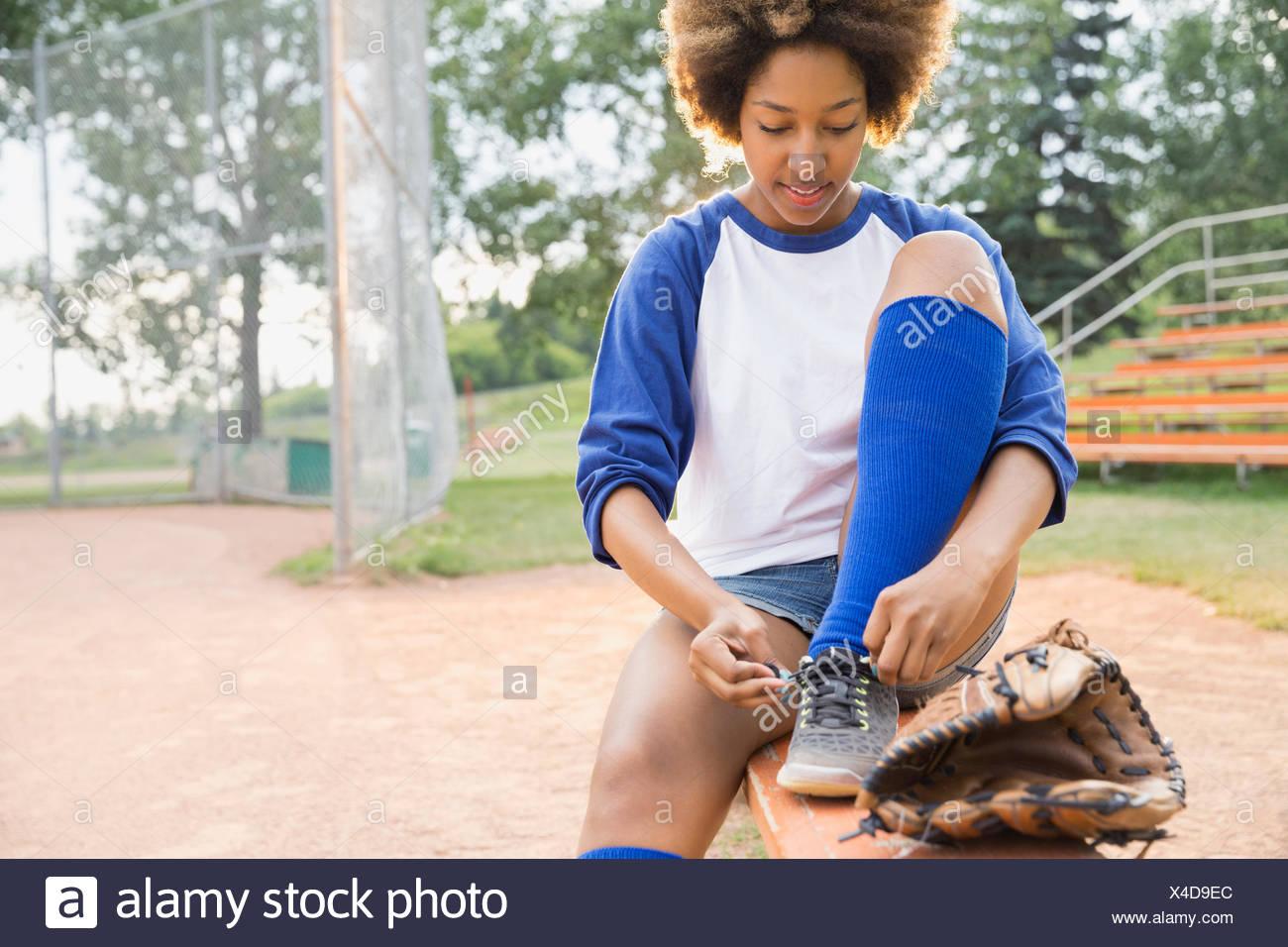 Joueur de base-ball chaussures de liage sur terrain Photo Stock