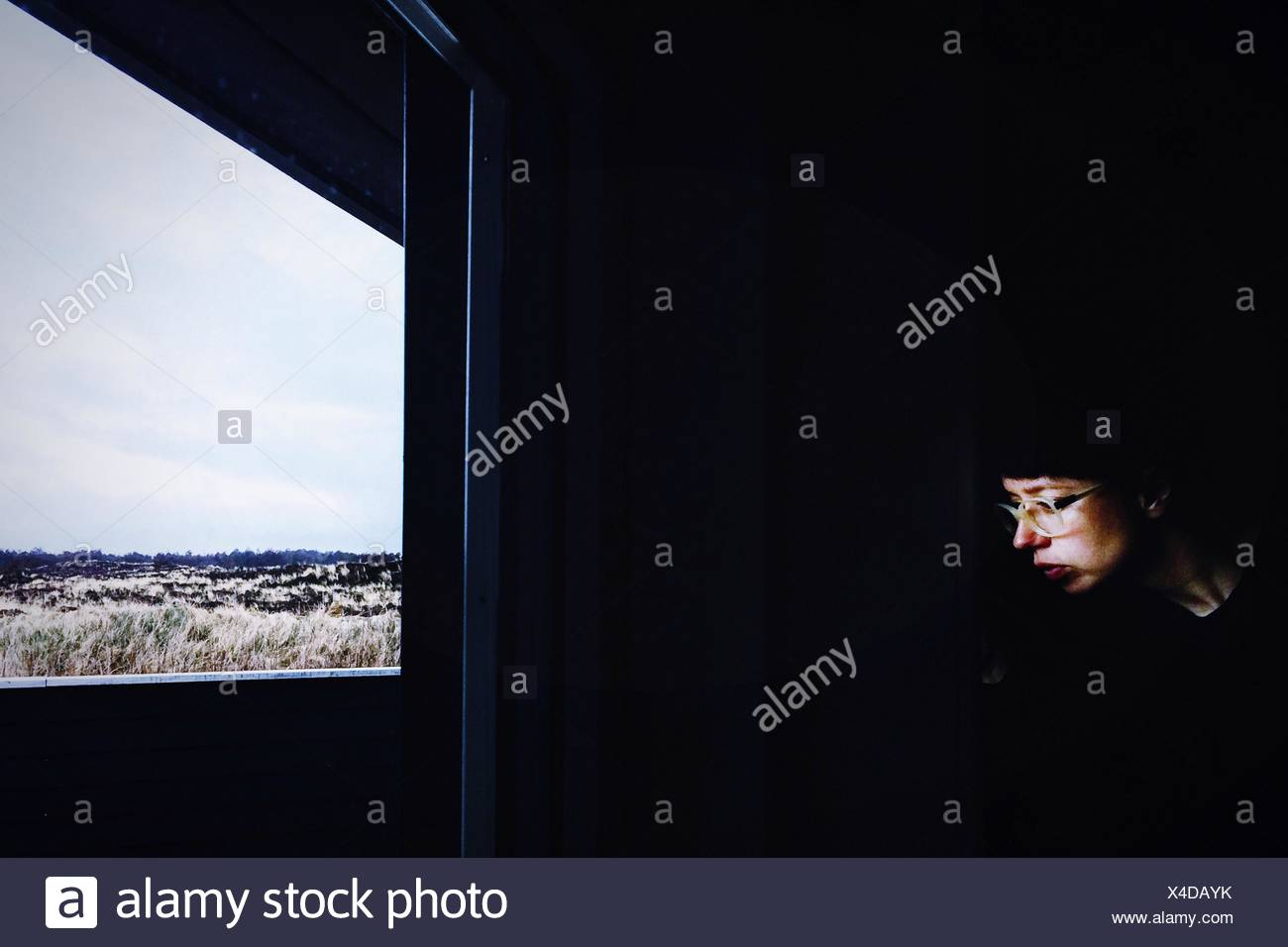 Thoughtful Woman Wearing Eyeglasses assis en face de la fenêtre à la maison Photo Stock