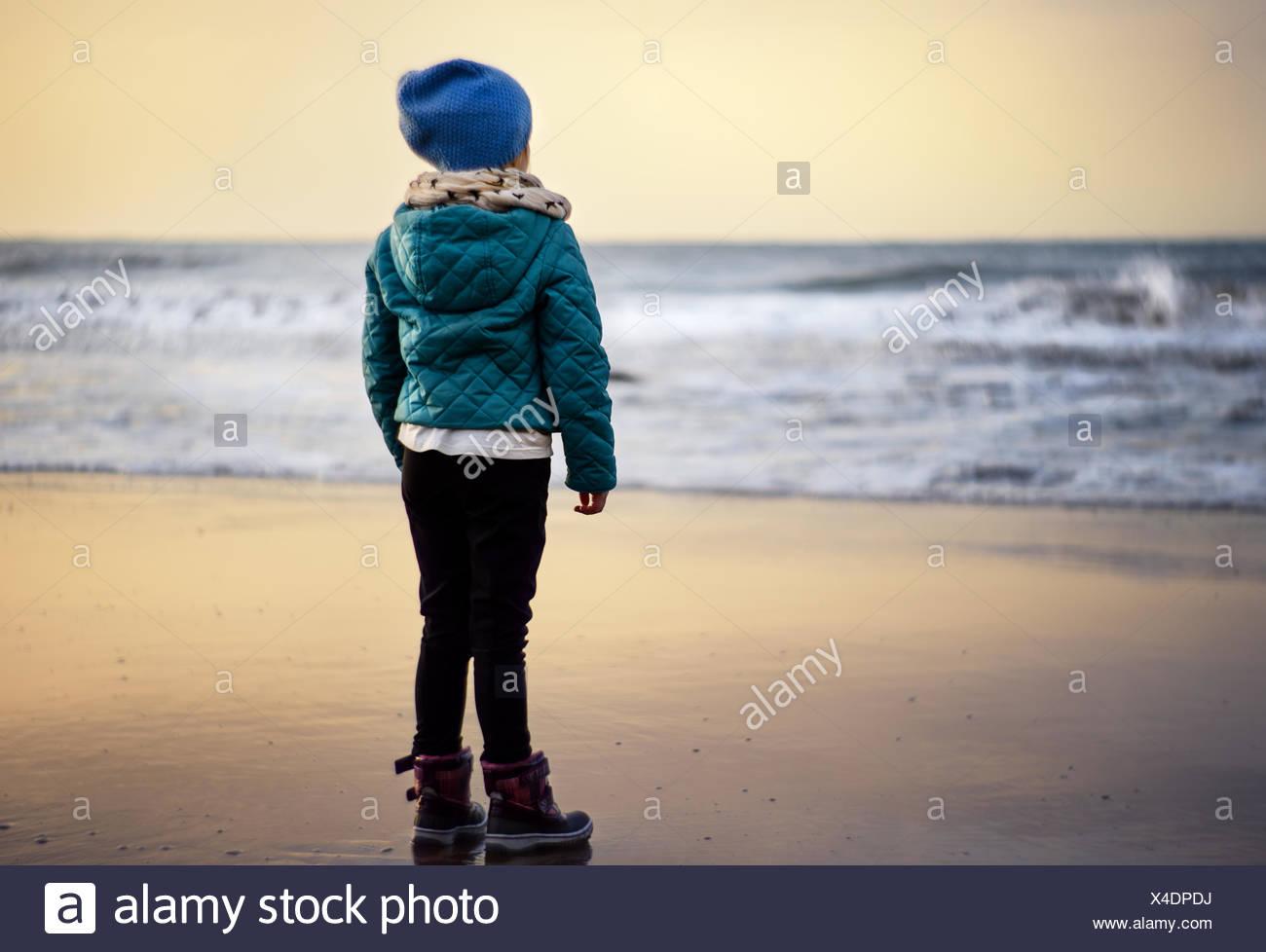 Girl (2-3) à la recherche de plage au coucher du soleil Banque D'Images