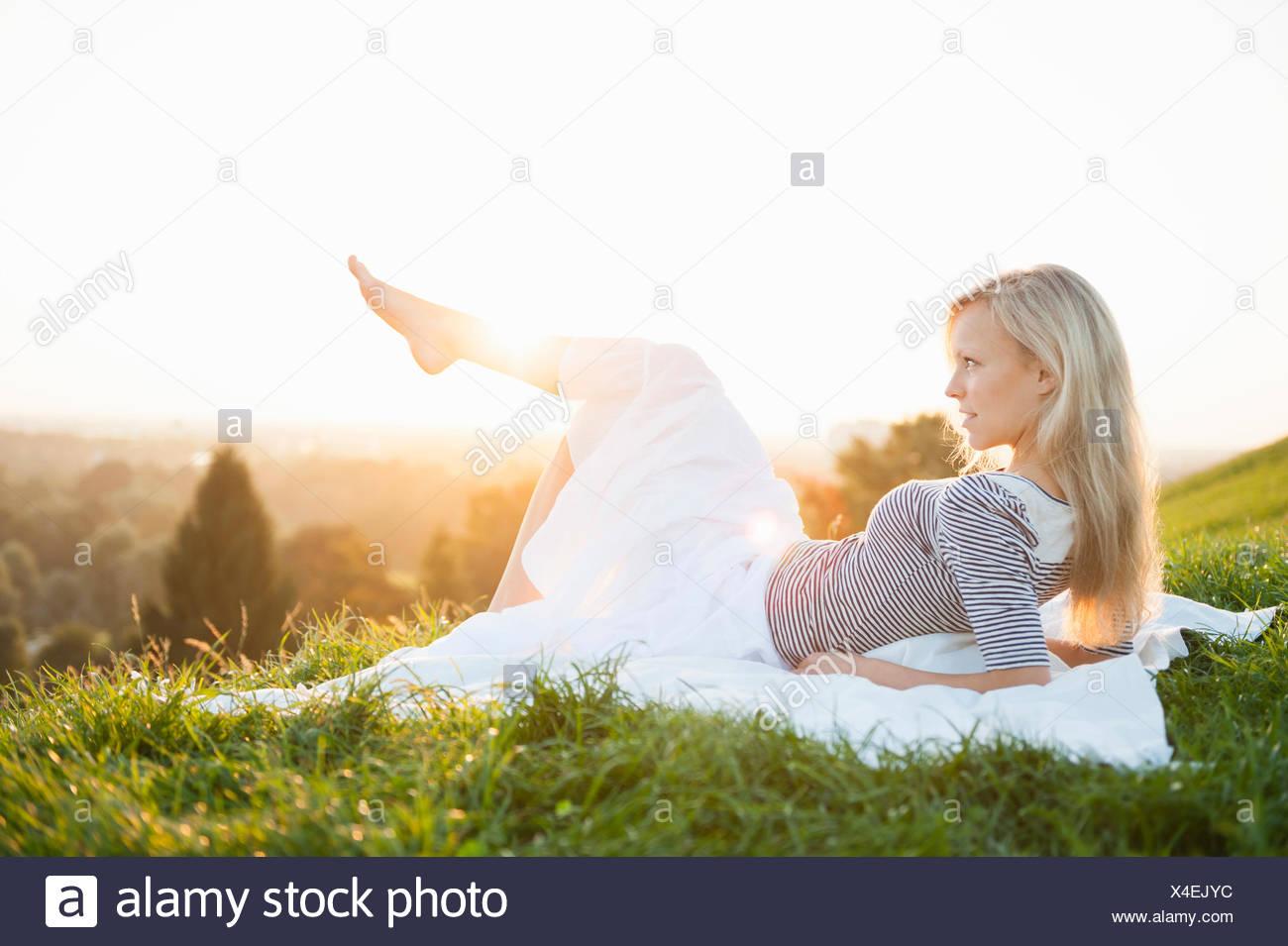 Jeune femme couchée sur park hill avec jambe soulevée Photo Stock