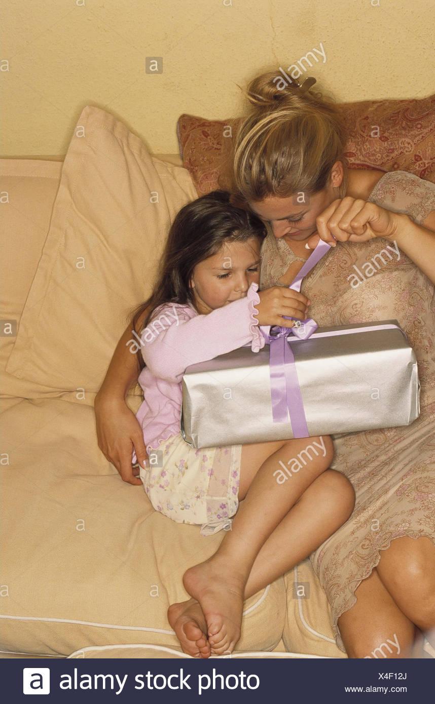 Canapé, écrou, filiale, présent, déballez, modèle libéré, femme, enfant, fille, cadeau d'anniversaire, anniversaire, surprise, l'emballage, en boucle, le mode de vie, d'attente, l'intérêt, la curiosité Photo Stock