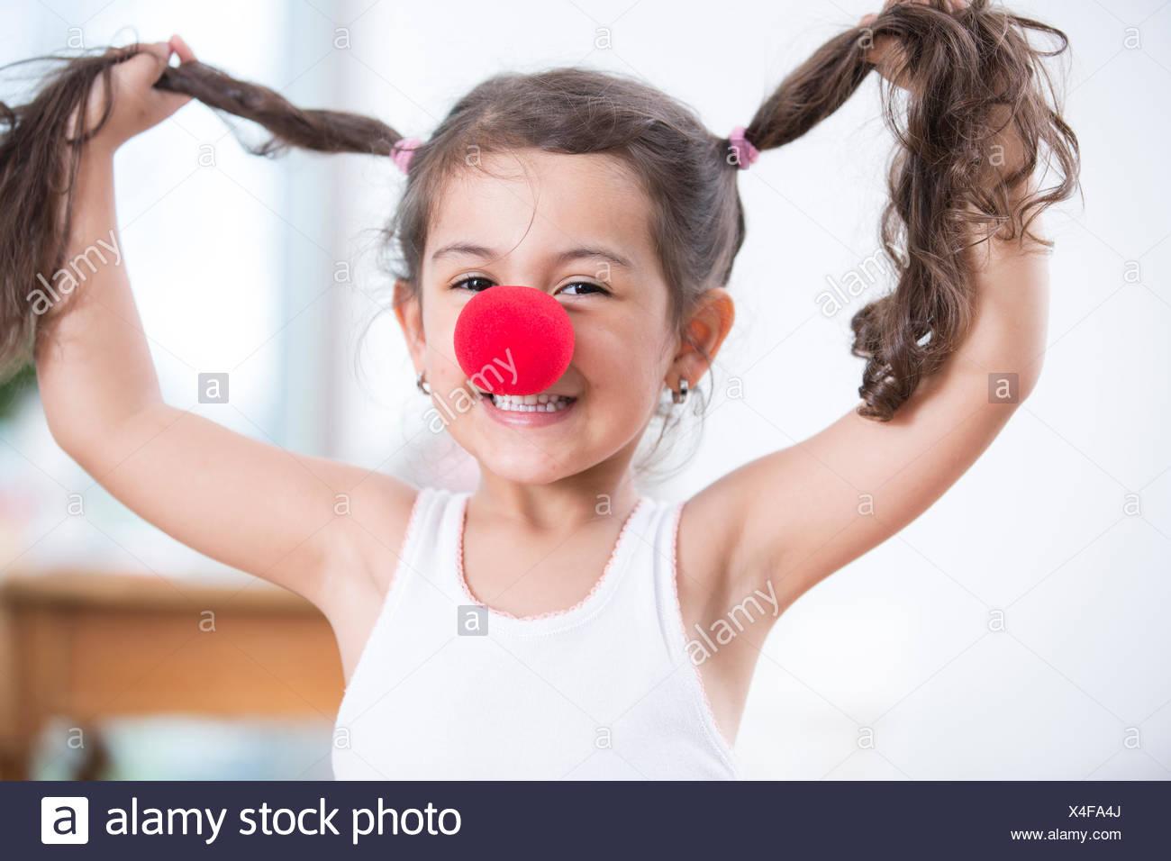 Portrait of playful little girl wearing clown nose holding des tresses à la maison Photo Stock