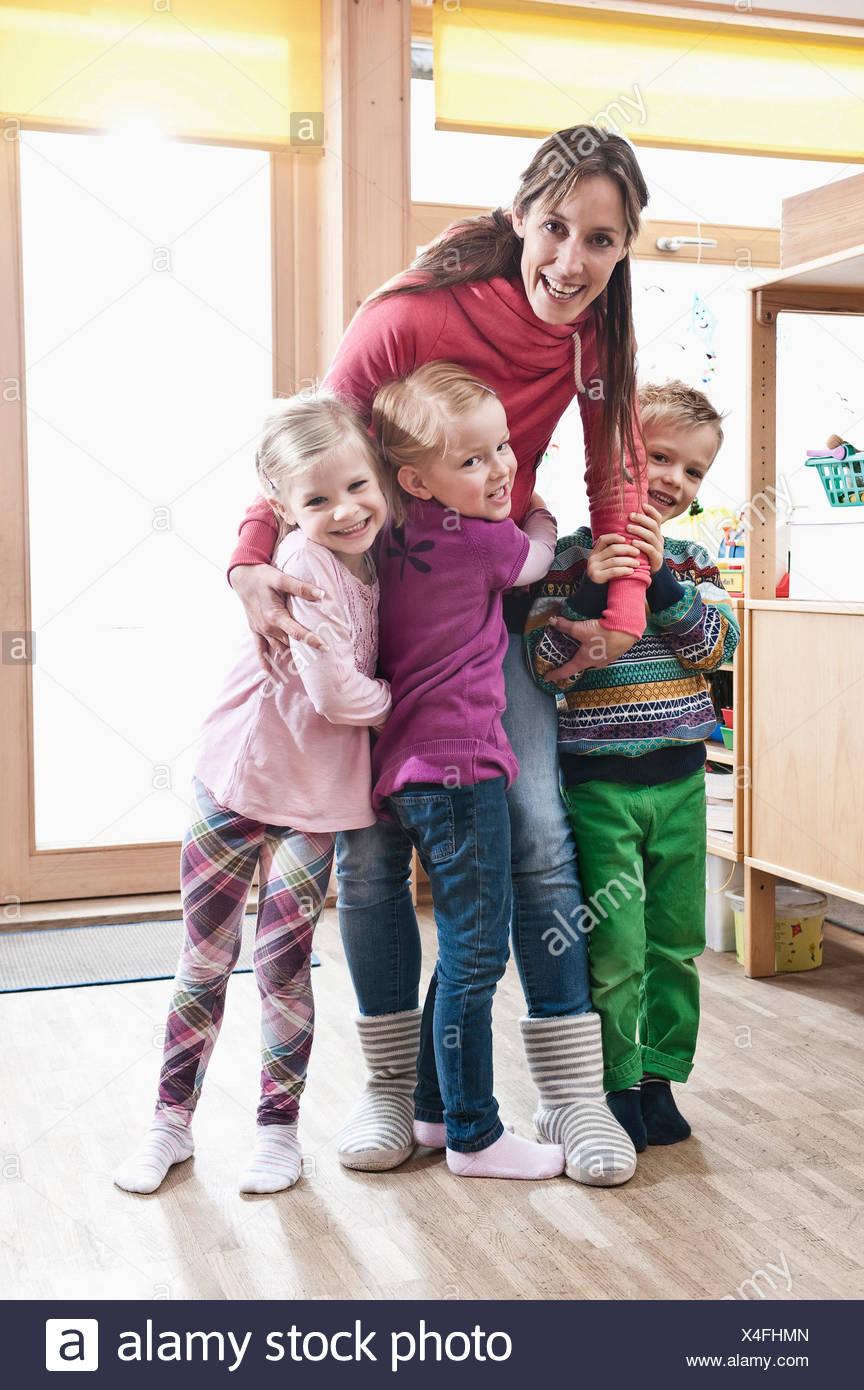 Photo de groupe des femmes d'éducateur et de trois enfants à l'école maternelle permanent Photo Stock