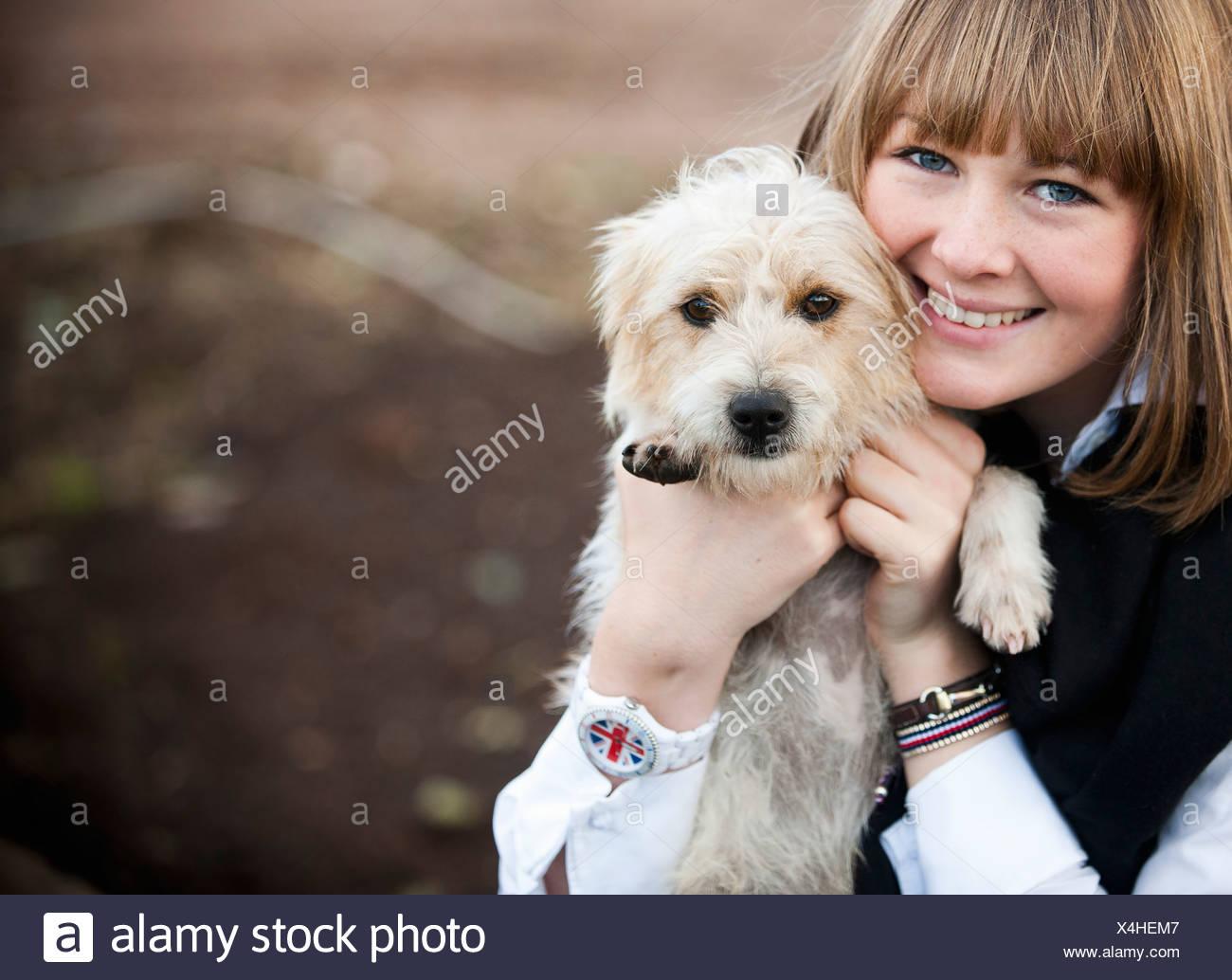 Une femme serrant un petit chiot terrier poilue. Photo Stock