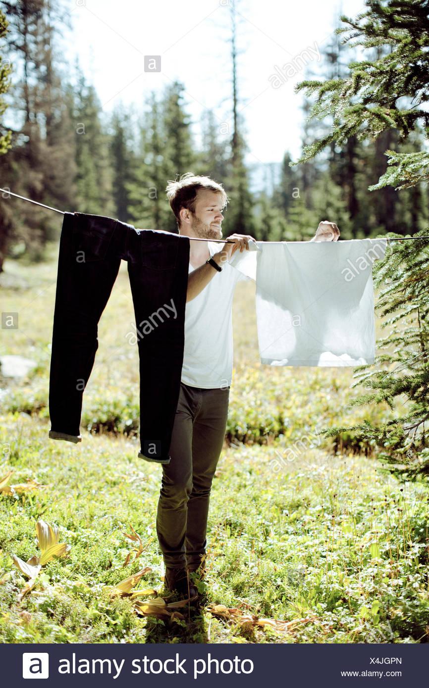 Étendre le linge à l'homme dans le pré Photo Stock