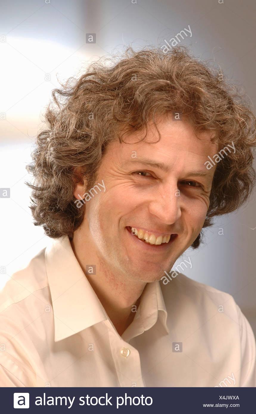 L'homme souriant avec des cheveux bouclés, 30-40, portrait Photo Stock