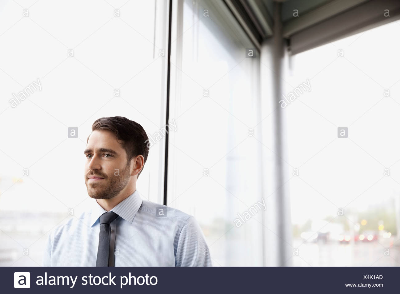 Thoughtful businessman standing by window Photo Stock
