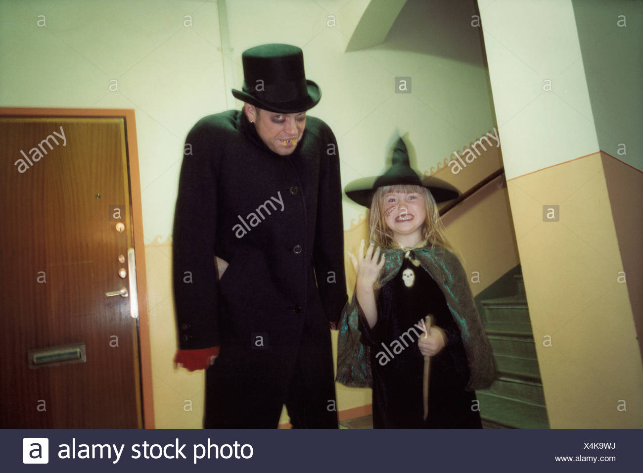 Un homme dans un costume de vampire et une jeune fille dans un costume de sorcière Photo Stock