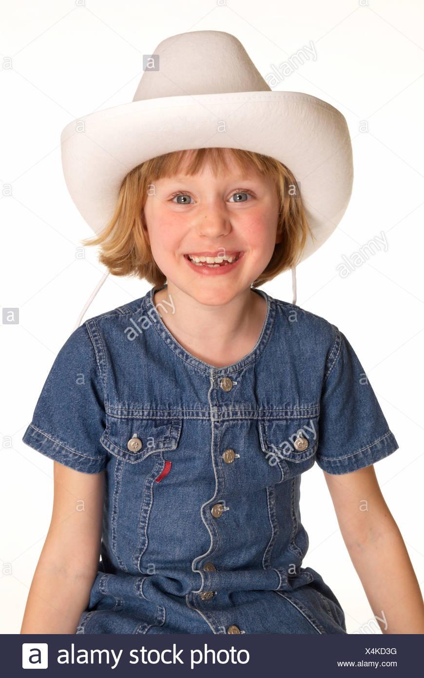 f475dbdf6dc2b Portrait d une petite fille souriante en robe en jean et hat against white  background