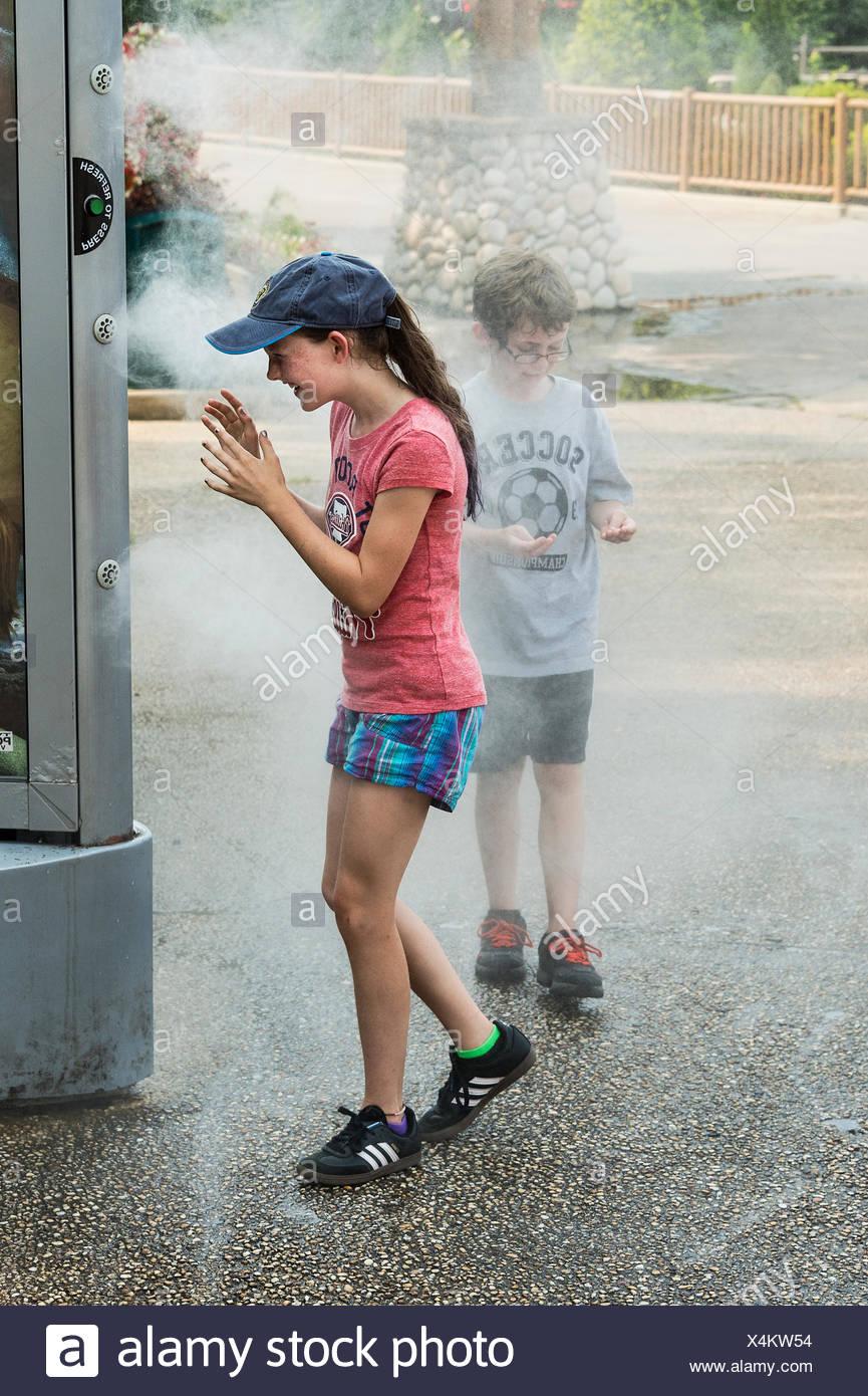 Les enfants se rafraîchir avec l'aide d'une brume rafraîchissante à la machine d'un parc. Photo Stock