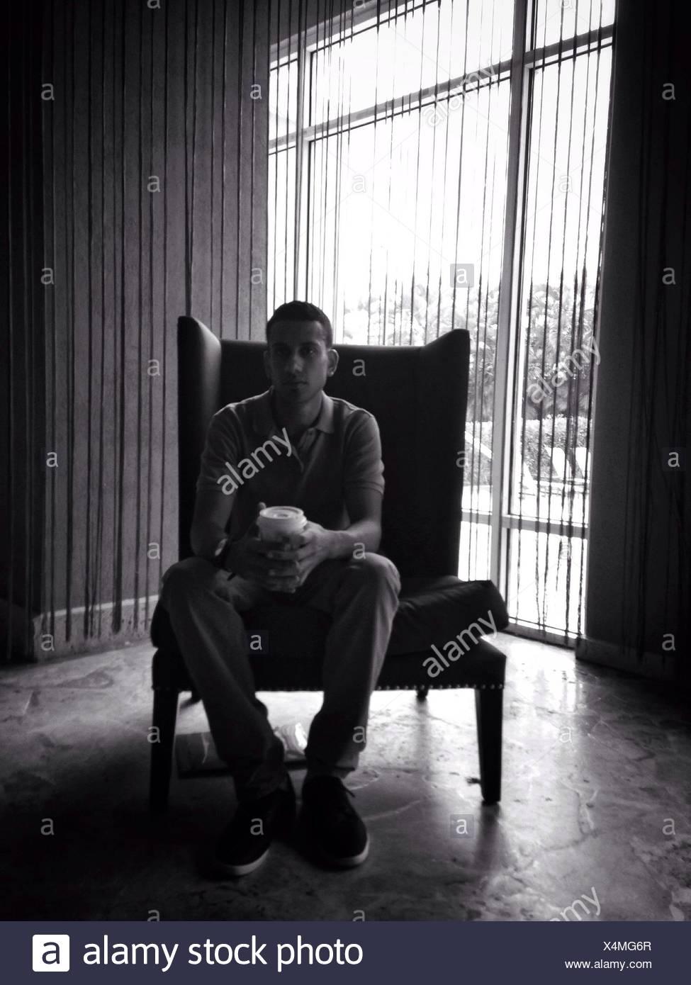Portrait de jeune homme avec café assis sur Wingback Chair At Home Photo Stock