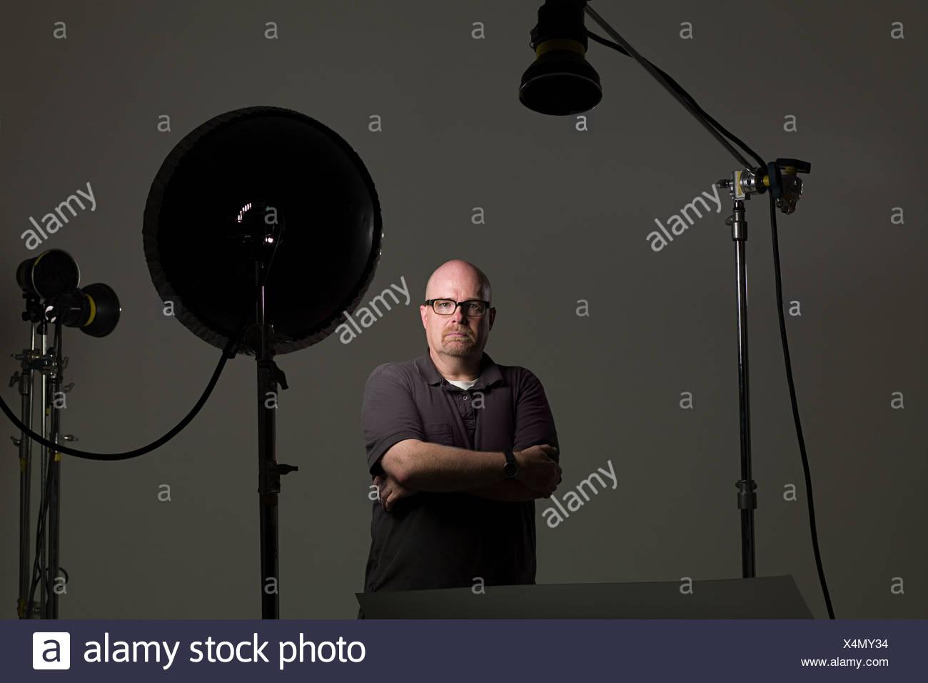 Portrait d'un homme à côté de l'équipement photographique Photo Stock