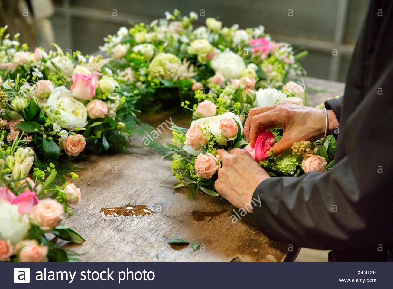 L'arrangement floral commercial. Un fleuriste, une femme travaillant sur une décoration florale à un établi. Photo Stock
