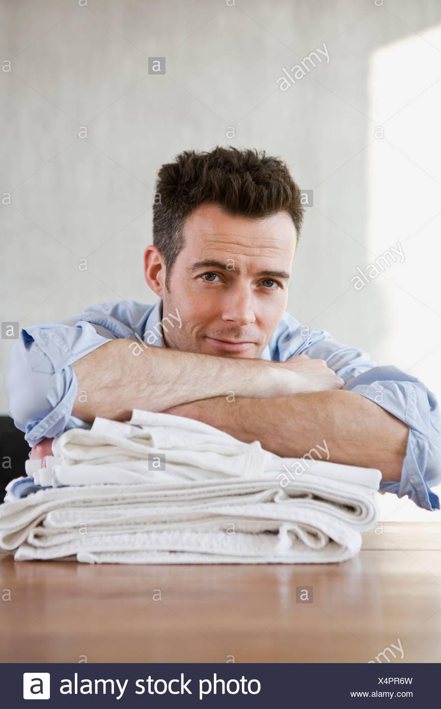 A smiling man reposant sur une pile de linge plié Banque D'Images