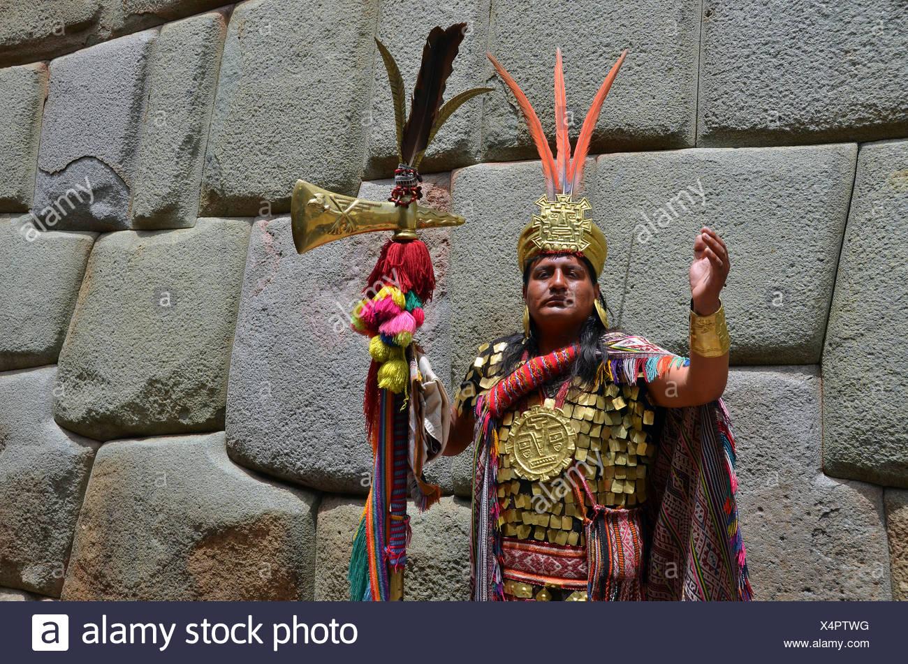 Indio homme habillé comme un chemin inca en face d'un mur antique des incas, centre touristique de Cuzco, Pérou, Amérique du Sud Photo Stock