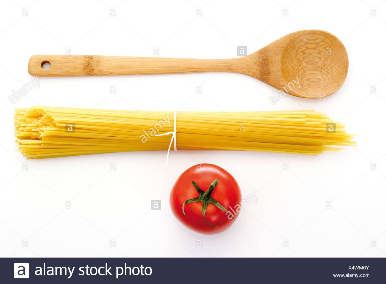 Paquet de spaghetti, cuillère en bois et la tomate, elevated view Banque D'Images