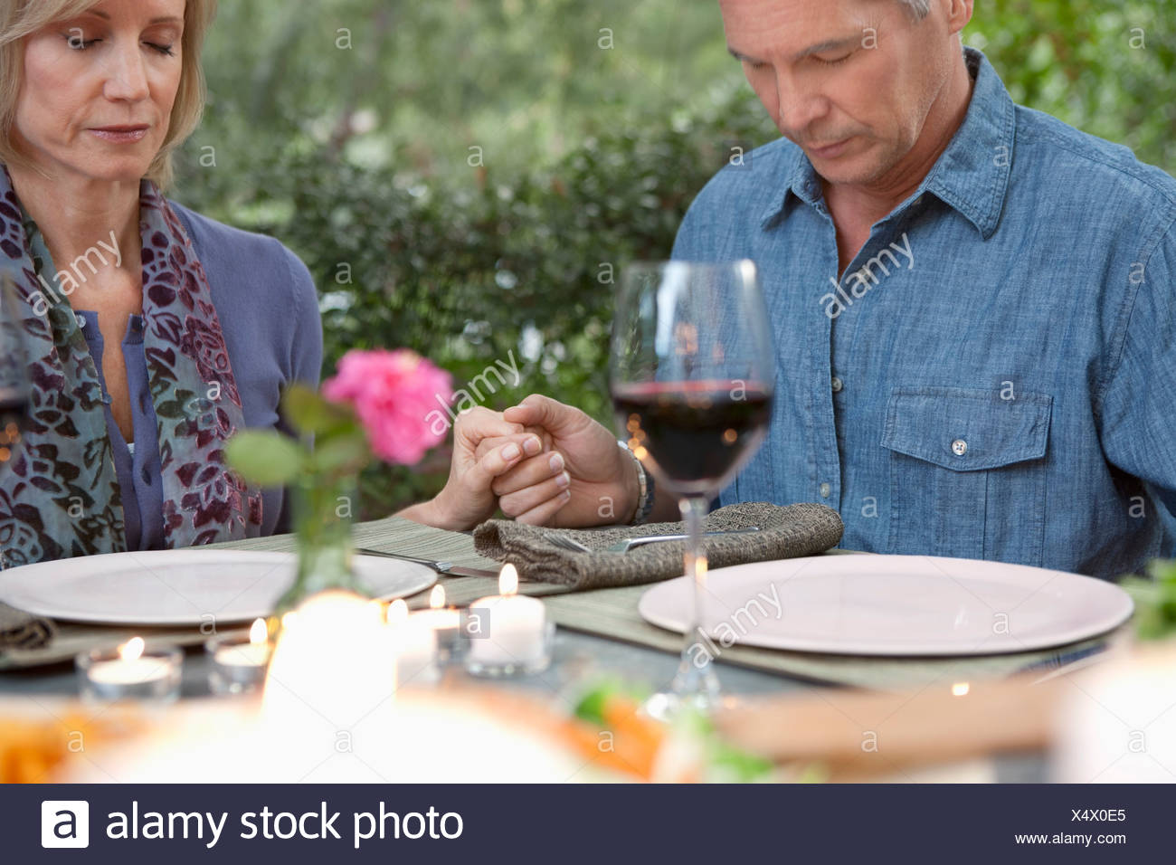 Vieux couple priant at dinner table Photo Stock