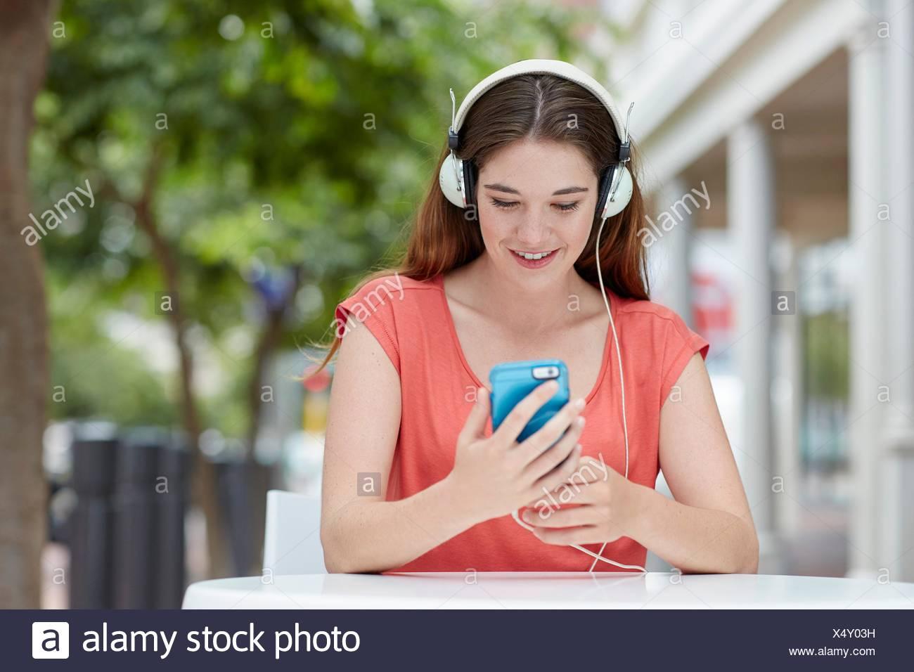 Parution du modèle. Young woman wearing headphones listening to music sur smartphone. Banque D'Images